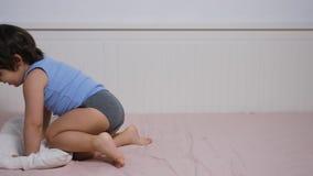 Jongenssprongen op het hoofdkussen die zich op een groot bed bevinden stock videobeelden