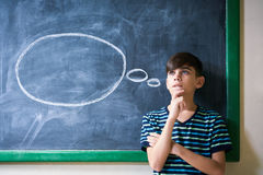 Jongensstudent Leaning On Blackboard en het Denken op School stock afbeeldingen
