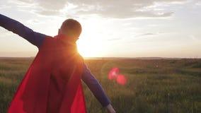 Jongenssuperhero op een gebied bij zonsondergang stock video
