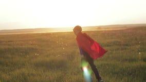 Jongenssuperhero op een gebied bij zonsondergang stock videobeelden
