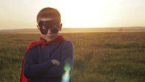 Jongenssuperhero op een gebied bij zonsondergang stock footage