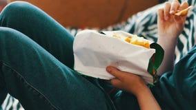 Jongenstiener die chips met handen op bank thuis eten stock video