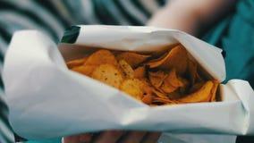 Jongenstiener die chips met handen op bank thuis eten stock footage