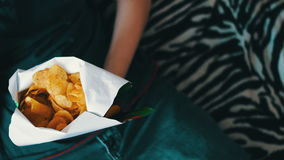 Jongenstiener die chips met handen op bank thuis eten stock videobeelden
