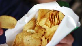 Jongenstiener die chips met handen op bank thuis ongezond voedsel eten stock video