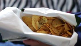 Jongenstiener die chips met handen op bank thuis ongezond voedsel eten stock footage