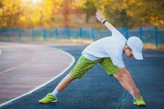 Jongenstiener die sportenoefeningen op een stadion doen Stock Foto