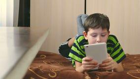 Jongenstiener het spelen op tablet stock videobeelden