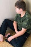 Jongenstiener met depressiezitting in de hoek van ruimte Stock Foto's