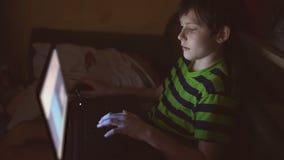 Jongenstiener met laptop het binnenspel van computerspelen op Internet stock videobeelden