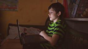 Jongenstiener met laptop spel van computer het binnenspelen op Internet stock videobeelden