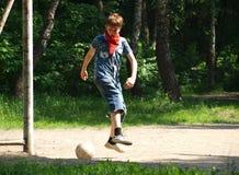 Jongenstiener voor het raken van een voetbalbal die wordt gestuiterd stock afbeelding
