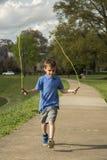 Jongenstouwtjespringen in het Park Stock Fotografie