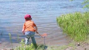 Jongensvisnet op de rivierbank Mooi de zomerlandschap Openlucht recreatie stock videobeelden