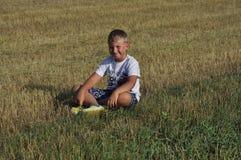 Jongenszitting in de weide Stock Afbeelding