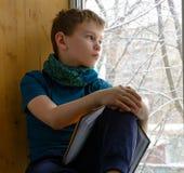 Jongenszitting dichtbij venster met boek en het kijken op de winterdag, binnen Stock Afbeelding