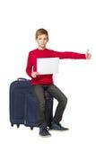 Jongenszitting die op reiszakken blad van document duim tegenhouden Royalty-vrije Stock Foto