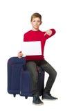 Jongenszitting die op reiszakken leeg blad van document houden Stock Foto's