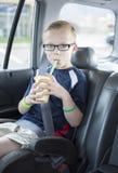 Jongenszitting in een autozetel die een smoothie op een lange autorit drinken royalty-vrije stock afbeeldingen