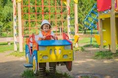 Jongenszitting in een houten auto in de speelplaats Stock Foto