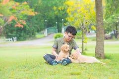 Jongenszitting en het spreken met zijn hond in park stock foto