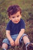 Jongenszitting in het gras Stock Afbeeldingen