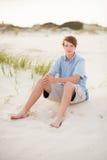 Jongenszitting in het zand stock foto