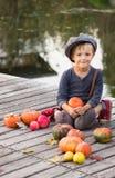 Jongenszitting met Halloween-pompoenen Stock Afbeelding