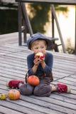 Jongenszitting met pompoenen en appelen Royalty-vrije Stock Foto's