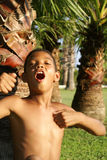 Jongenszitting onder palm Royalty-vrije Stock Afbeelding