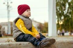 Jongenszitting op de stappen op de straat royalty-vrije stock afbeelding