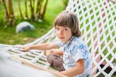 Jongenszitting op een hangmat. Stock Afbeeldingen