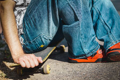 Jongenszitting op een skateboard Stock Foto's