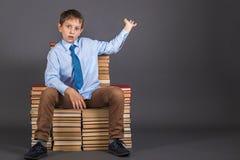 Jongenszitting op een troon van boeken royalty-vrije stock foto