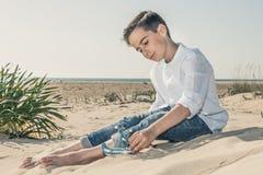 Jongenszitting op het strandzand in een witte kleding stock foto's