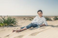 Jongenszitting op het strandzand in een witte kleding royalty-vrije stock fotografie