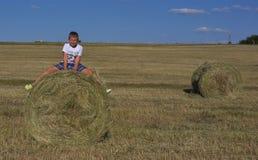 Jongenszitting op hooiberg in de weide Royalty-vrije Stock Afbeeldingen