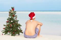 Jongenszitting op Strand met Kerstboom en Hoed stock afbeeldingen