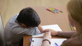 Jongenszitting in stilte tijdens zitting met jonge psycholoog die de hand houden stock footage