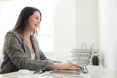 Jonger meisje die in het bureau bij de lijst werken stock fotografie