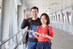 Jongere Aziatische reizende man en vrouw die zich met toothy smili bevinden royalty-vrije stock foto's