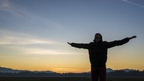 Jongere die de zonsopgang of de zonsondergang vieren Stock Afbeelding