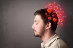 Jongere die over liefde met rode harten denken royalty-vrije stock afbeelding