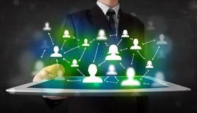 Jongere die tablet met groene sociale media pictogrammen voorstellen stock afbeelding