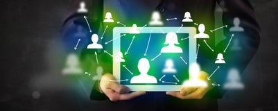 Jongere die tablet met groene sociale media pictogrammen voorstellen stock foto's