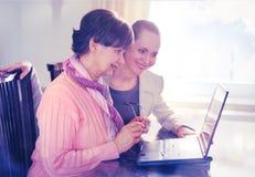Jongere vrouw die een bejaarde persoon helpen die laptop computer voor Internet-onderzoek met behulp van stock fotografie