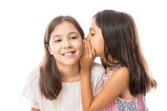 Jongere zuster het fluisteren roddel aan haar oudere zuster op witte bedelaars stock foto