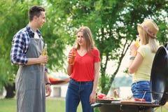 Jongeren die barbecue met moderne grill hebben Royalty-vrije Stock Foto's