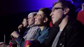 Jongeren die bij de bioskoop zitten, op een film letten en pop graan eten stock footage