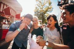 Jongeren die candyfloss bij kermisterrein delen stock afbeelding